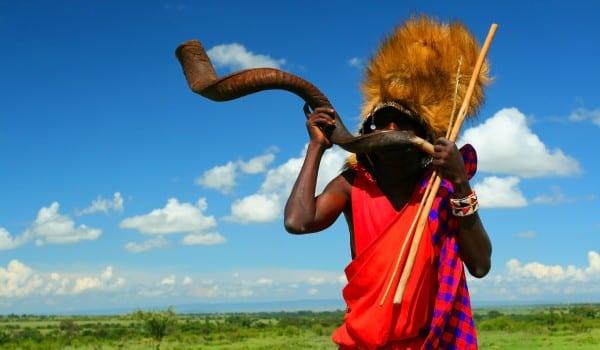 Masai warrior playing traditional horn. Africa. Kenya